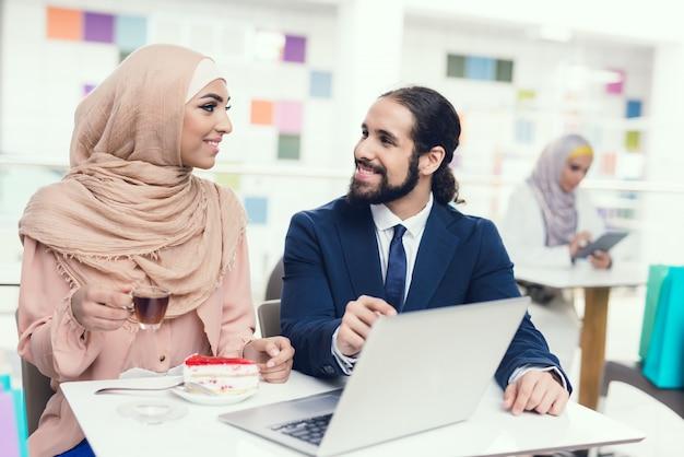 Vrouw in hijab met pak man in winkelcentrum.