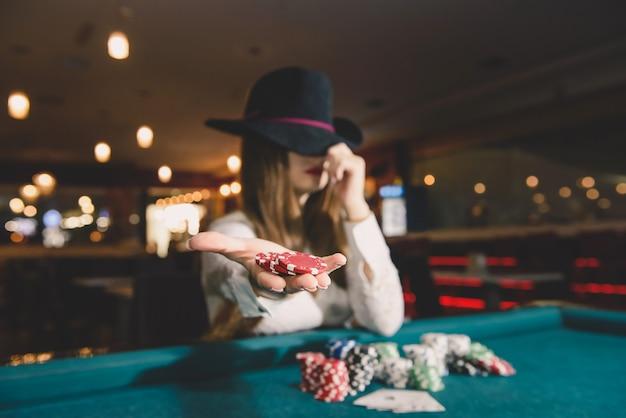 Vrouw in hoed die casinofiches op palm aanbiedt
