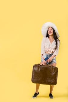 Vrouw in hoed die en koffer bevindt zich houdt