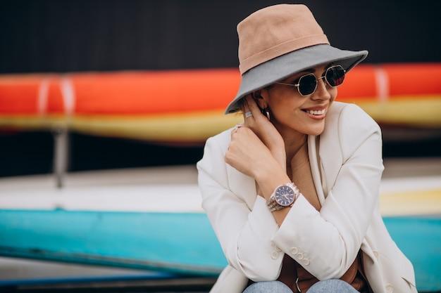 Vrouw in hoed die en telefoon glimlacht gebruikt
