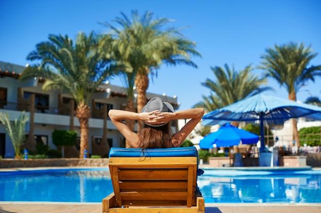 Vrouw in hoed die op een lanterfanter dichtbij het zwembad bij het hotel ligt