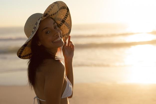 Vrouw in hoed die zich op het strand bevindt
