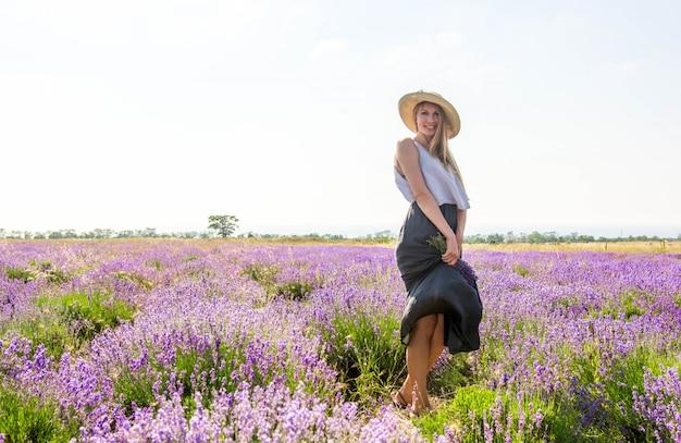 Vrouw in hoed en jurk op lavendel veld