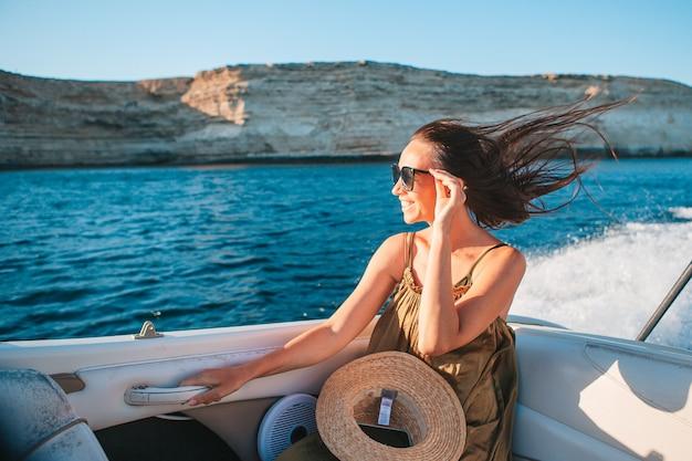 Vrouw in hoed en kleding die op boot in duidelijke open zee zeilen