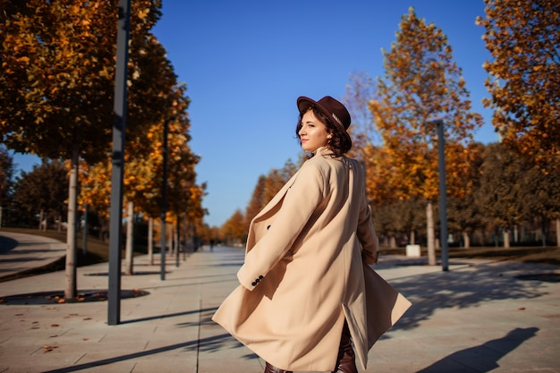 Vrouw in hoed en lichte vacht op een wandeling in het stadspark