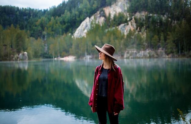 Vrouw in hoed en rood overhemd dichtbij meer in bergen.