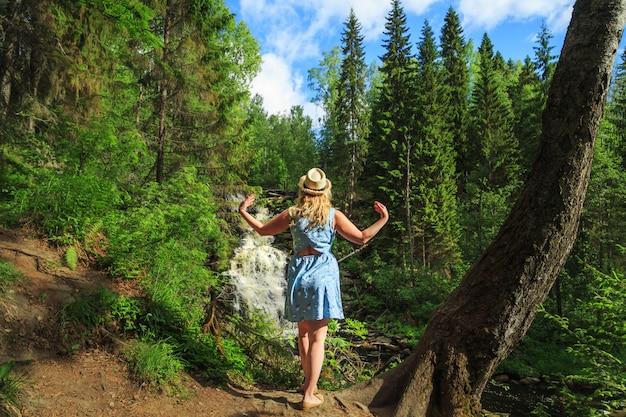 Vrouw in hoed mediteert in de buurt van bos waterval.