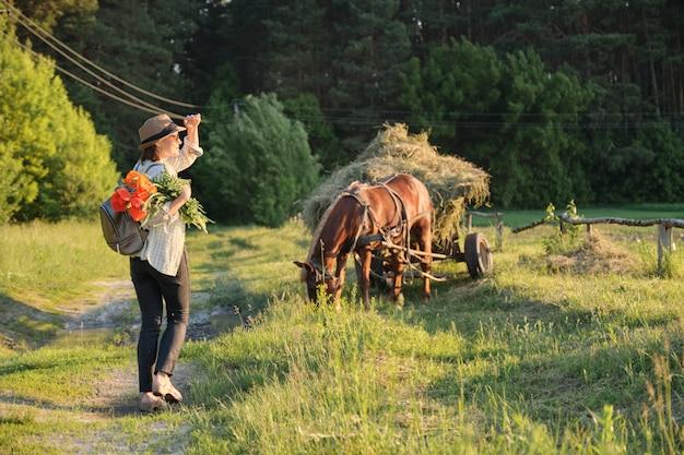 Vrouw in hoed met boeket van rode papavers bloemen lopen