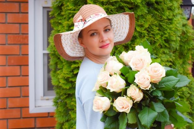 Vrouw in hoed met een boeket bloemen