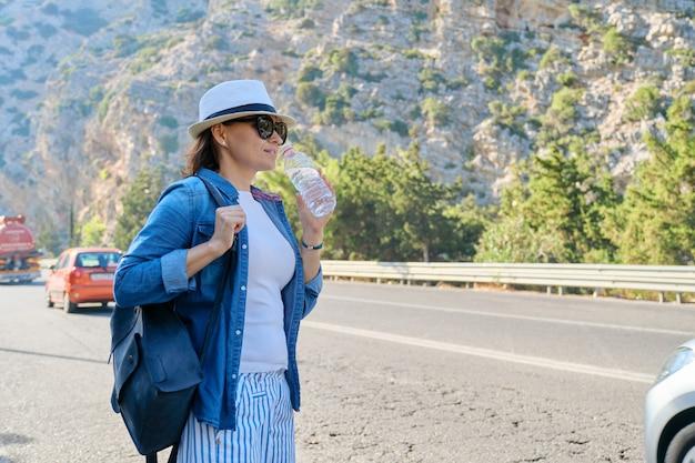 Vrouw in hoed met fles water in bergen op snelweg, liften, de bus stoppen, met kopieerruimte. natuur, weg, toerisme, reizen, avontuur, road trip concept achtergrond