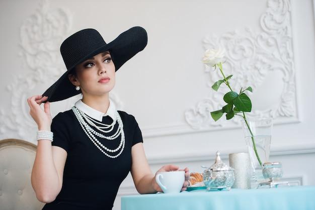 Vrouw in hoed, net als de beroemde actrice, croissant die eet en thee drinkt.