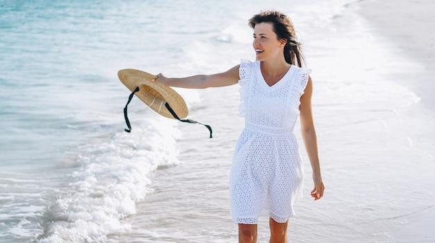 Vrouw in hoed op de kust van de indische oceaan