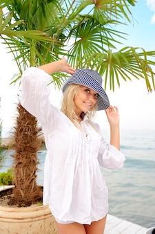 Vrouw in hoed op zee strand.