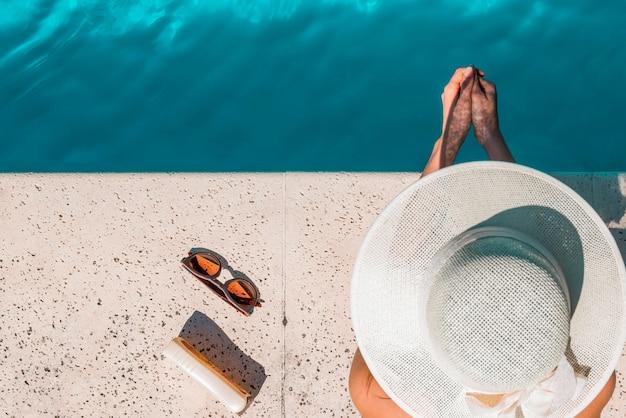 Vrouw in hoed zittend op de rand van het zwembad