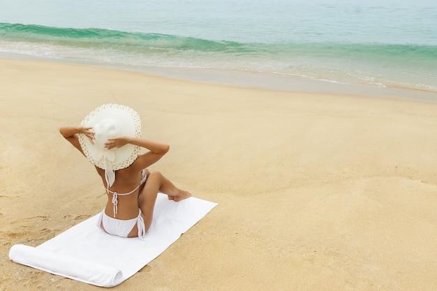 Vrouw in hoed zittend op het strand geniet van uitzicht op het zeegezicht