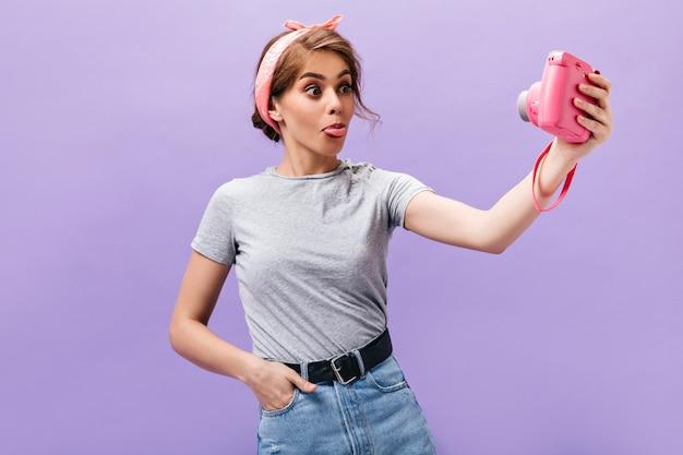 Vrouw in hoge geest toont tong en neemt selfie. grappige prachtige dame in roze bandana en modieuze outfit poseren. n paarse achtergrond.