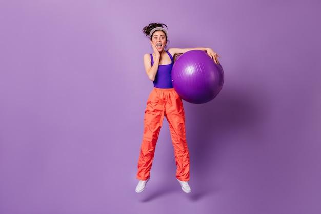 Vrouw in hoge geesten springt met fitball op paarse muur