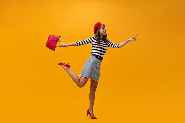 Vrouw in hoge geesten wijst naar plaats voor tekst op een oranje achtergrond. glimlachend modieus meisje in gestreepte trui en rode hakken poseren.