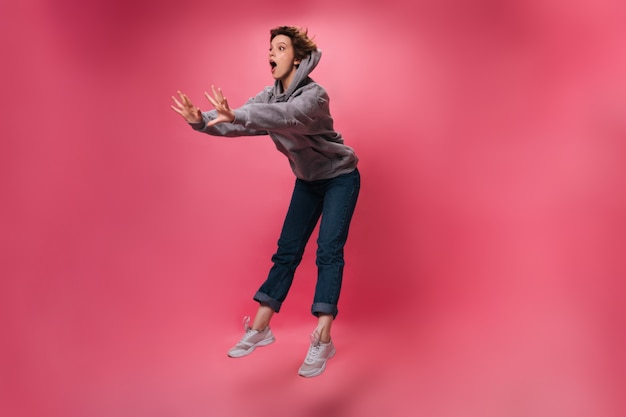Vrouw in hoodie en spijkerbroek kijkt verbaasd en springt op geïsoleerde achtergrond. emotionele geschokt meisje in denim broek beweegt op roze achtergrond