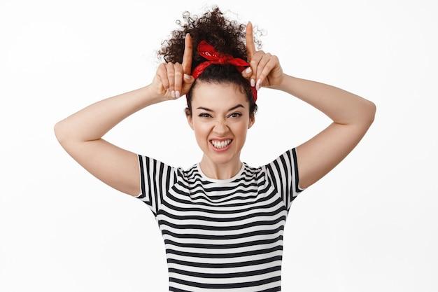 Vrouw in hoofdband met tong, gebaar van stierenhoorns, koppig en speels kijkend, staande op wit