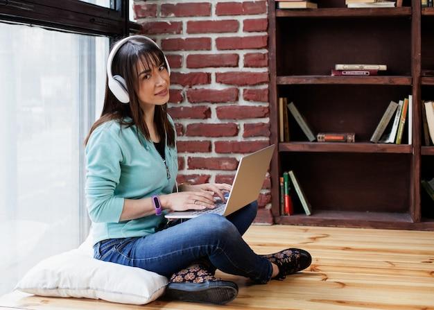 Vrouw in hoofdtelefoon werkt op een laptop