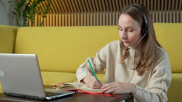 Vrouw in hoofdtelefoon zittend op gele bank thuis en video-chatten op laptopcomputer.