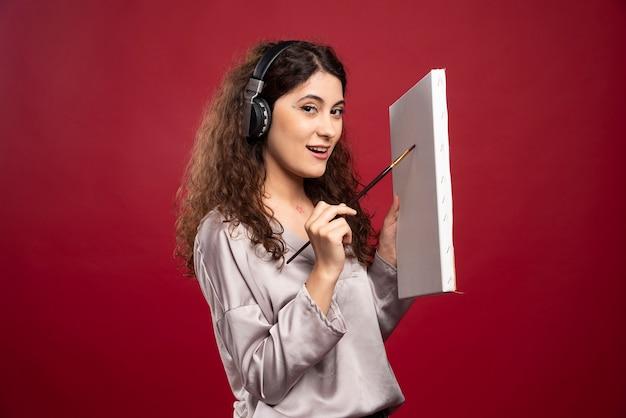 Vrouw in hoofdtelefoons die op canvas schilderen.
