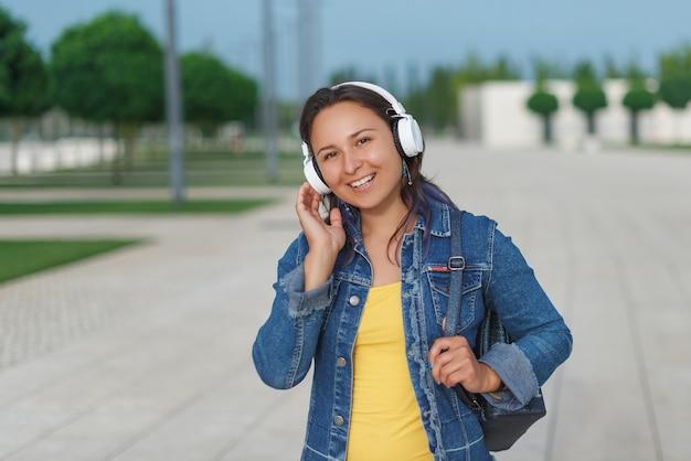 Vrouw in hoofdtelefoons. emotionele jonge vrouw in koptelefoon luisteren muziek buiten op een groen gras.
