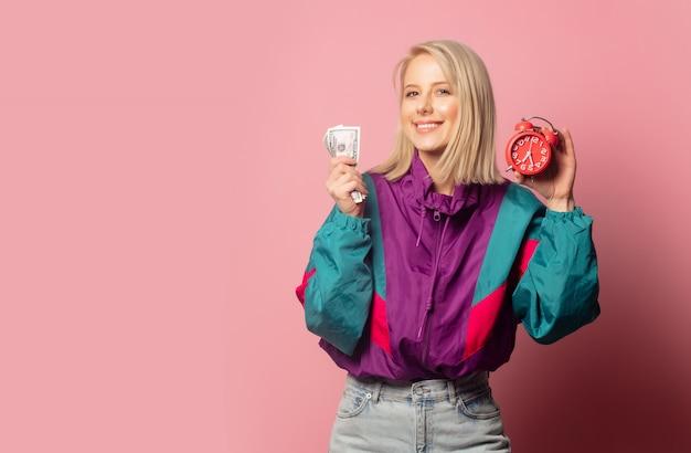 Vrouw in jaren 90 kleding met wekker en contant geld