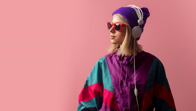 Vrouw in jaren 90 kleding met zonnebril en koptelefoon