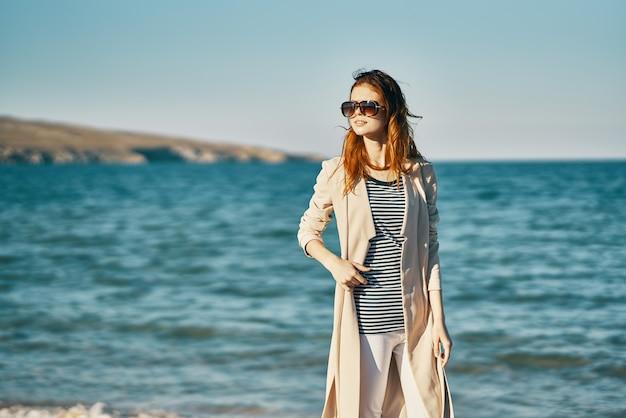 Vrouw in jas in t-shirt en broek op het strand in de buurt van de zee landschap bergen op de achtergrond