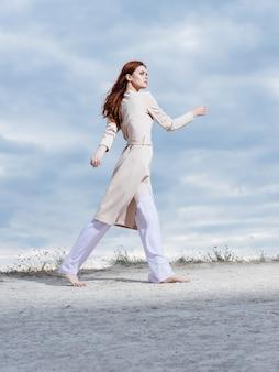 Vrouw in jas poseren strand frisse lucht lifestyle fashion