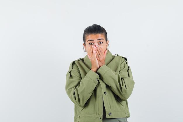 Vrouw in jas, t-shirt hand in hand op mond en bang op zoek
