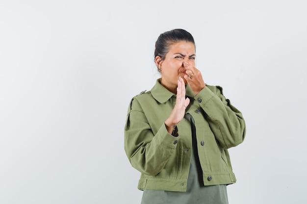 Vrouw in jasje, t-shirt die neus dichtknijpt door slechte geur en walgelijk kijkt