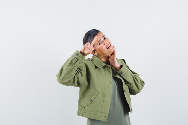 Vrouw in jasje, t-shirt die overwinningsgebaar toont en er zelfverzekerd uitziet