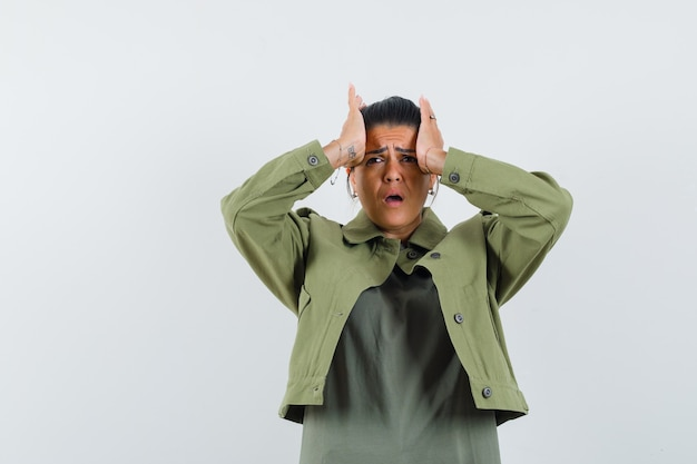 Vrouw in jasje, t-shirt hand in hand op het hoofd en op zoek weemoedig
