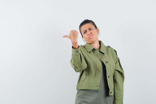 Vrouw in jasje, t-shirt met duim midden en aarzelend op zoek