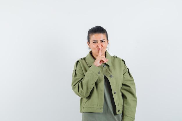Vrouw in jasje, t-shirt met stilte gebaar en op zoek zelfverzekerd