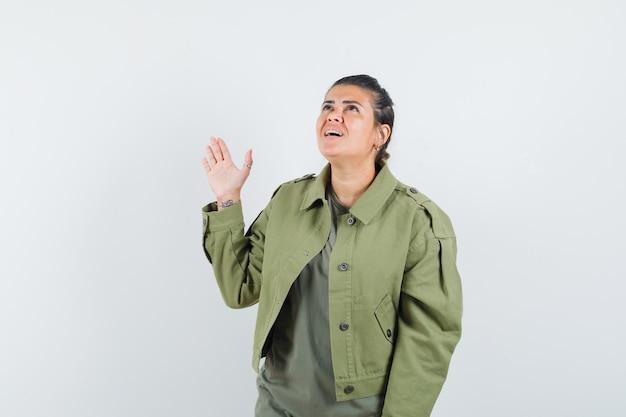 Vrouw in jasje, t-shirt zwaaiende hand terwijl je omhoog kijkt en hoopvol kijkt