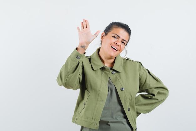 Vrouw in jasje, t-shirt zwaaiende hand voor groet en op zoek vrolijk