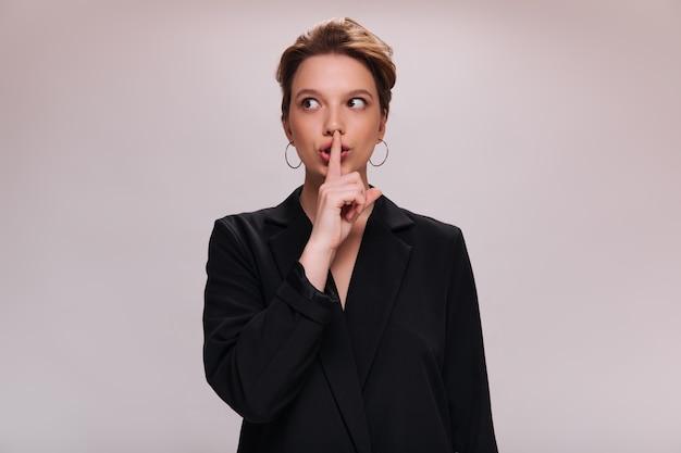 Vrouw in jasje vraagt om geheim te houden. mooi meisje in zwart pak wil stilte horen. dame in oversized outfit vormt op geïsoleerde achtergrond