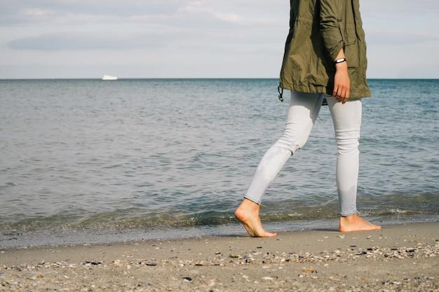 Vrouw in jeans en een jas loopt op het strand blootsvoets