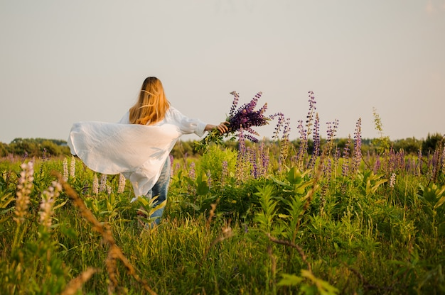 Vrouw in jeans en witte mantel die het veld doornemen