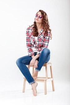 Vrouw in jeans geruite overhemd en zonnebril