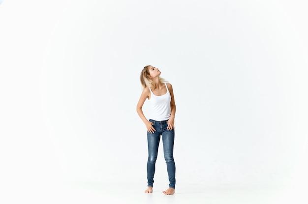 Vrouw in jeans op blote voeten staat op de vloer mode emoties beweging