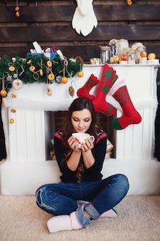 Vrouw in jeans zit met een kopje warme drank voor de open haard versierd met kerstfeestjes