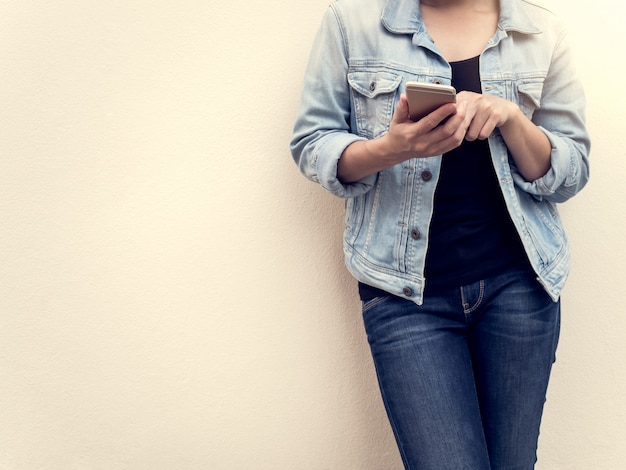 Vrouw in jeansmanier die mobiele telefoon met behulp van