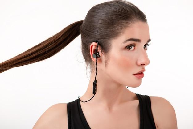 Vrouw in jogging zwarte top luisteren naar muziek op koptelefoon poseren geïsoleerd op wit