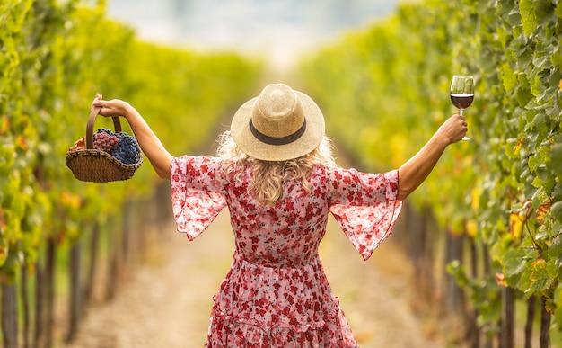 Vrouw in jurk en strohoed heeft handen opgestoken en houdt een glas heerlijke rode wijn en een mand vol druiven vast. ze loopt door een wijngaard.