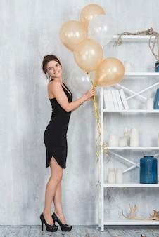 Vrouw in jurk met ballonnen